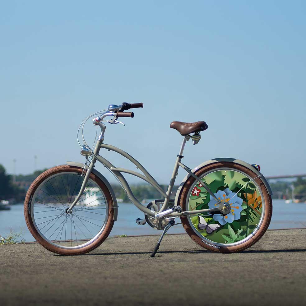 Vélo Beach Cruiser mixte pour homme ou femme au design fleuri. Collection Canopée avec une roue lenticulaire à l'arrière, pour vous démarquer lors de vos trajets