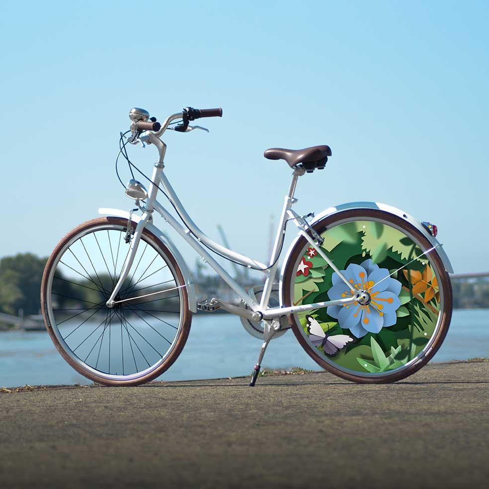 Vélo de ville Coffee Mixte, collection Canopée. 1 roue arrière pleine au design fleuri. 1 roue lenticulaire pour ne pas passer inaperçu lors de vos déplacements urbains