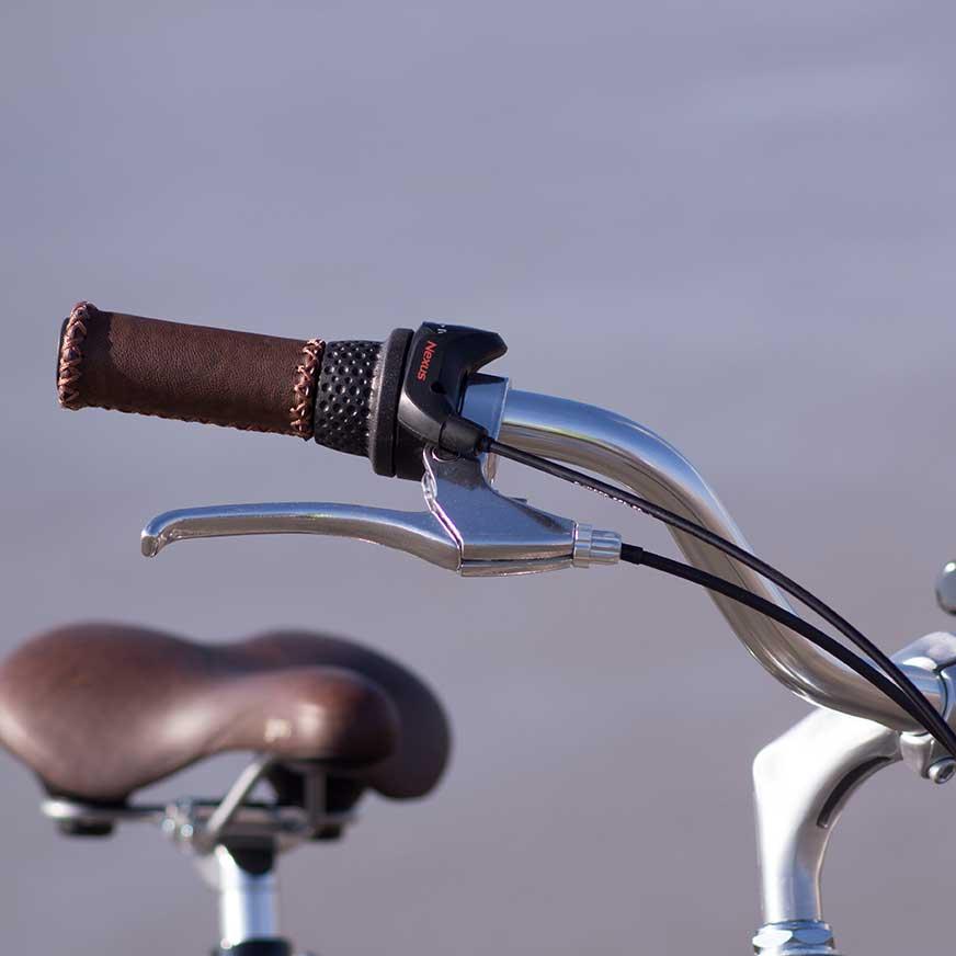 Détails du guidon du vélo de ville Coffee homme. Des poignées en cuir ainsi que des vitesses Nexus, pour vos voyages en ville ultra confortables et un look vintage