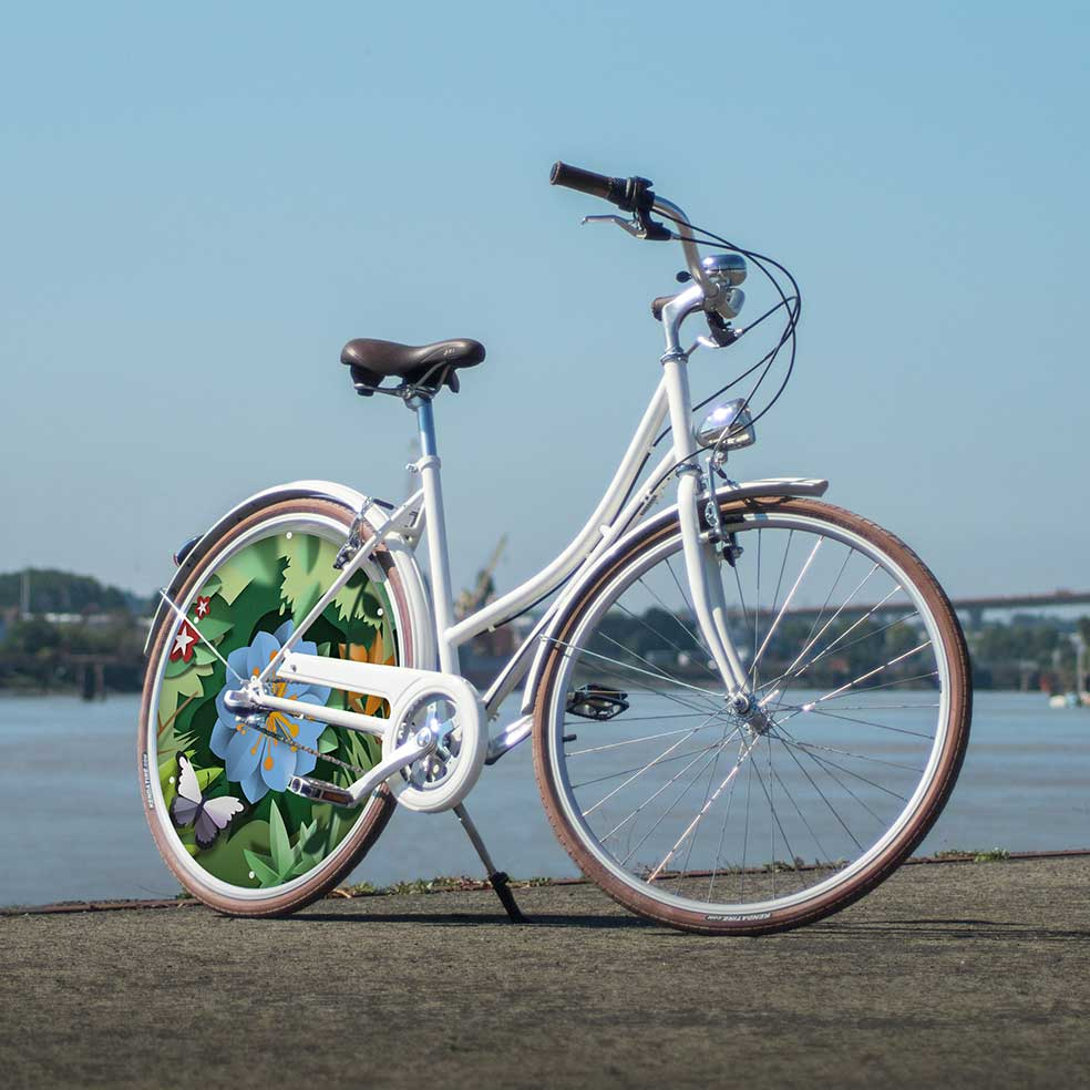 Vélo de ville Coffee Mixte, avec une roue lenticulaire. Un enjoliveur au design canopée fleuri pour effectuer vos trajets avec un vélo de ville au style hollandais