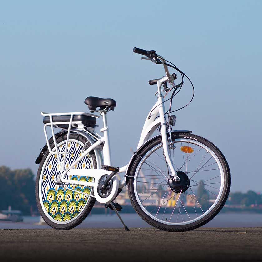 Le vélo électrique E-Colors dans sa version Indigo. Une roue pleine à l'arrière avec un enjoliveur aux allures modernes. Déplacez-vous sur batterie pendant 40 kilomètres, puis pédalez par vous-même en toute simplicité