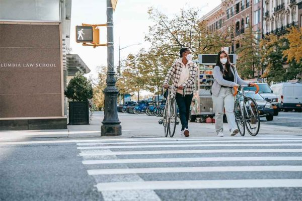 Personnes marchant à côté de leurs vélos pendant crise sanitaire