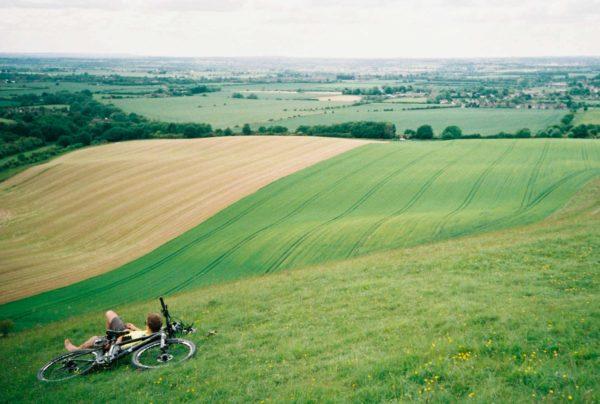paysage d'un grand champ vert avec au milieu un homme qui se prélasse à côté de son vélo VTT